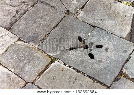 A pothole in a road. Broken stone pavement dangerous to motorists