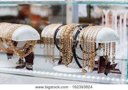 Many various golden chains in a shopwindow