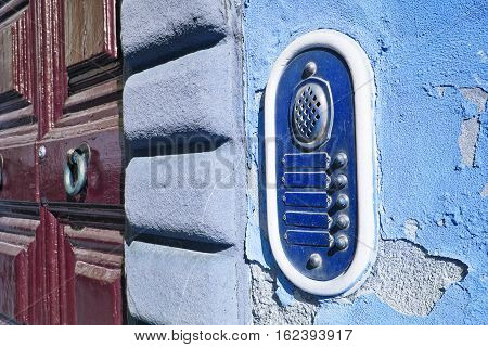 Old colored bell system on blue plaster (Tuscany - Italy)