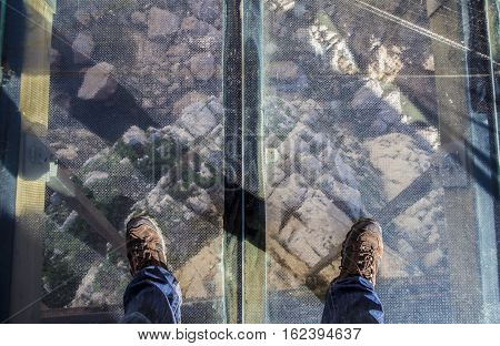 Trekking shoes over glass footbridge at Caminito del Rey path Malaga Spain
