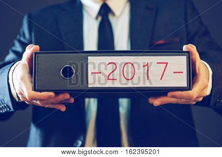 Businessman holding 2017 document ring binder folder with corporate plans visions and business strategy in new year