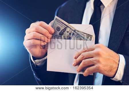 Bribery and corruption concept in business and politics with caucasian businessman and cash money in white envelope
