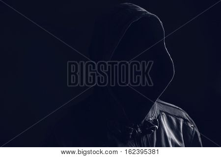 Unrecognizable faceless spooky hooded hooligan low key