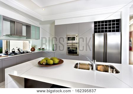 Counter top made in ceramic seen closely with fruits on a brown color clay dish next to the modern silver faucet attached to the sink the silver refrigerator and the wall oven with pantry cupboards next to the gas stove