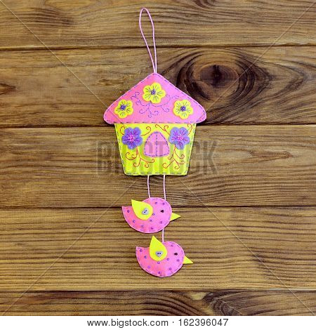 Bright house with birds ornament isolated on wooden background. Beautiful house with birds sewn from pink, purple and yellow felt. Home wall decoration. Spring kids crafts idea. Closeup