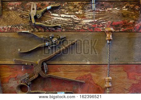 Old Tools hang on a wooden walls