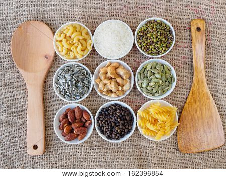 top view including Almond, black pepper seed, Sun flower seed, Cashew nuts, Pumpkin seeds, green bean, rice, fettucine, all put on small white cup and on brown hemp sack texture background