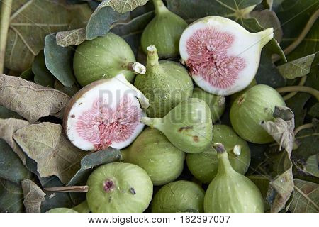 Cut figs on a fig leaf on a background of whole figs in the boxes for sale. Ripe figs in boxes for sale in the greek market
