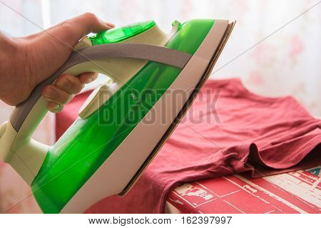 Shirt on ironing board and iron in the hand. Homelike atmosphere.