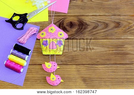 Colorful house with birds decoration, thread, scissors, felt sheets and scraps on the table. Beautiful house with birds sewn from felt and decorated with flowers and beads. Spring or summer kids DIY