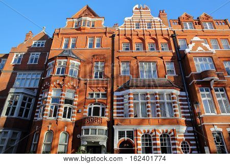 LONDON, UK - NOVEMBER 28, 2016: Red brick Victorian houses facades in the borough of Kensington and Chelsea