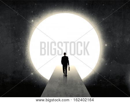 businessman standing in front of the huge circle gate