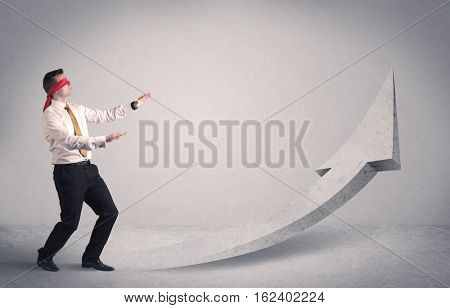A scared blindfolded businessman forced to face a problem concept with illustrated arrow pointng to the sky in empty space.