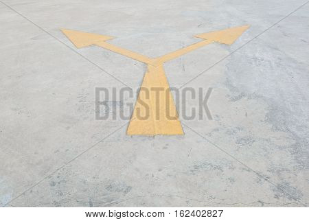 Closeup surface old and pale yellow painted arrow sign on cement street floor textured background with copy space