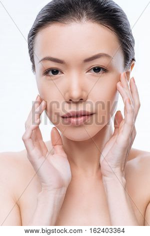 Wellness of my skin. Positive involved Mongolian woman touching her face and expressing peacefulness while standing against white background
