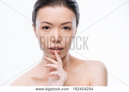 Full of charm. Delighted feminine young Korean woman touching her lip and expressing tenderness while standing isolated in white background