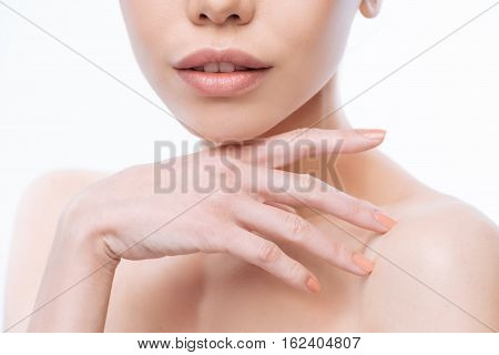 Full of graceful motions. Charming elegant concentrated Korean woman looking at the audience and expressing gracefulness while standing isolated in white background