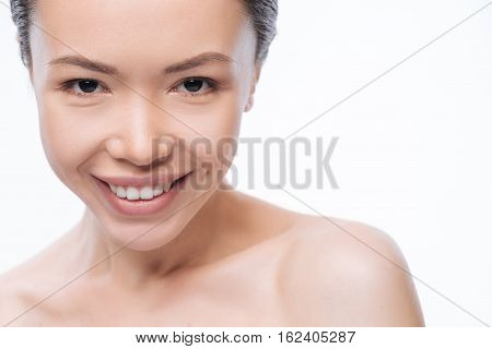 In a positive mood. Delighted glad young Korean woman expressing joy while standing against white background and smiling