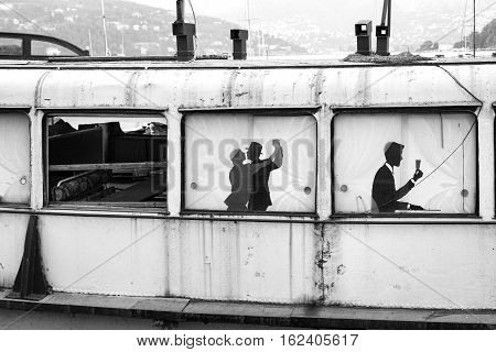 An old and ruined boat detail, formerly used as floating bar & restaurant, over the waters of Como Lake (Lombardy, Northern Italy). Black and white photo.