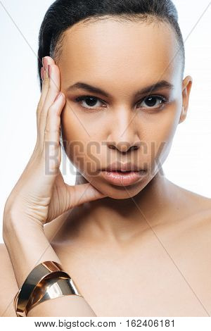 Graceful model. Elegant pathetic young Negroid woman touching her face while standing isolated in white background and expressing grace