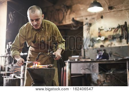 The blacksmith heats the gas burner the metal product on the anvil