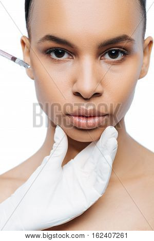 Beauty injection. Decisive motionless young Negroid woman standing against white background and expressing peacefulness while making the injection in her face