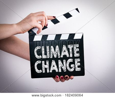 Climate change. Female hands holding movie clapper.