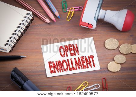 Open Enrollment. Wooden office desk with stationery, money and a note pad.