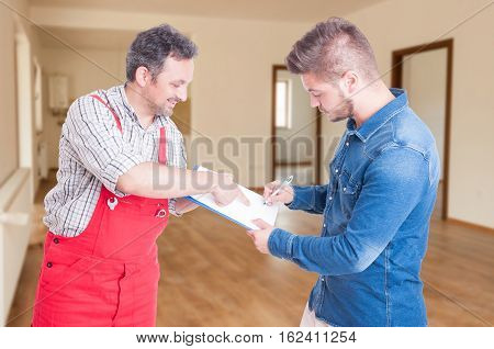 Confident Fitter Giving Clipboard With Contract To Client