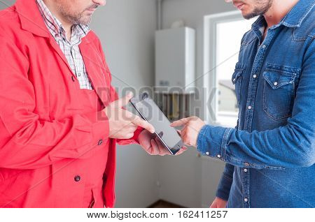 Male Customer With Plumber Browsing On Tablet
