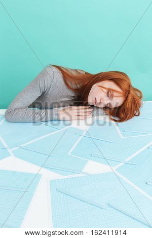Tired overworked young woman lying and sleeping on the table over blue background