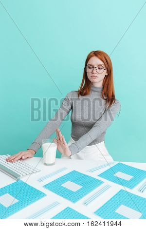 Cute young woman in glasses working with computer and refusing from milk over blue background