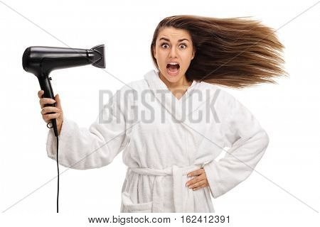 Shocked woman in a bathrobe drying her hair with a hairdryer isolated on white background