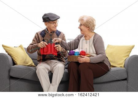 Mature woman showing a mature man how to knit isolated on white background