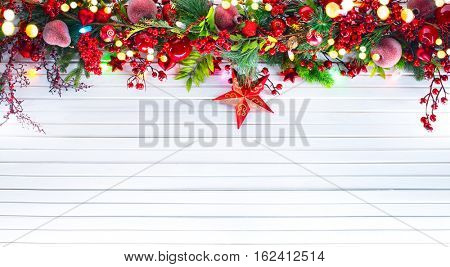 Christmas and New Year Decoration over white wood background. Border art design with holiday baubles. Beautiful Christmas tree closeup decorated with star, holly berry, tinsel. Space for your text.