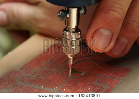 Electronic circuits procedure Use mini drill to broach on Printed Circuit Boards. Selective focus.