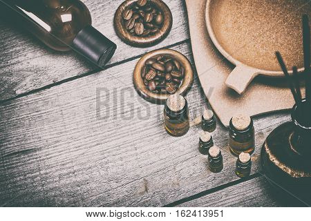 Aromatherapy and relaxation accessories. Natural essential oils, crock with incense sticks, bamboo bowl with water, massage oil bottle on old wooden planks. Copy space. Retro style processing