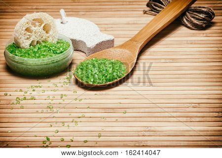 Natural products and accessories for peeling and exfoliation: sea salt, loofah, pumice on wooden background. Copy space. Retro style processing