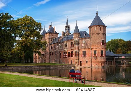 Elderly couple sitting on a bench in front of the medieval castle De Haar near Utrecht, the Netherlands