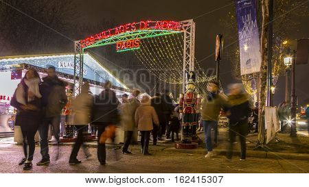ParisFrance - 27 November 2016: People walking at the entrance in the Christmas market on Champs Elysees in Paris.