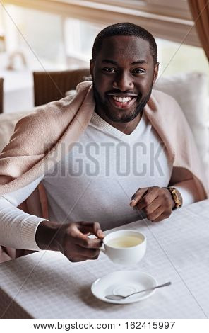 Enjoying the tea . Cheerful happy sincere African American man sitting in the cafe and being covered with a blanket while holding the cup of tea