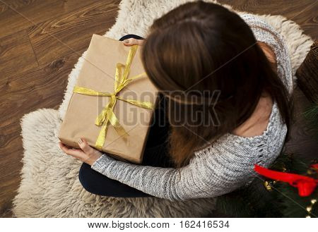 The young woman is unpacking the present in her hands