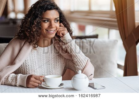Enjoying the tea in the cafe. Smiling cheerful positive African American woman sitting in the cafe and being covered with a blanket while enjoying the cup of tea and smiling