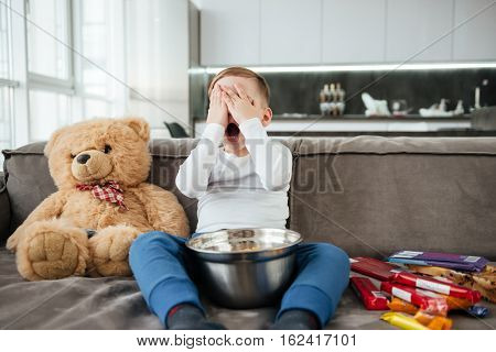 Photo of scared little boy on sofa with teddy bear at home watching TV while eating chips.