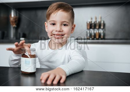 Image of little boy standing in kitchen while eating sweeties. Look at camera.