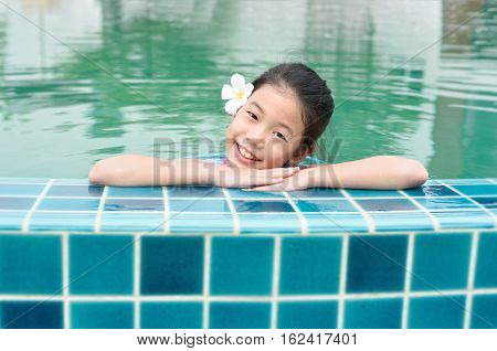 Pretty little Asian kid with perfect skin white teeth in swimming pool. Happy preteen girl smiling and looking at camera in a pool side. Portrait of child with white Plumeria flower and ceramic tile.