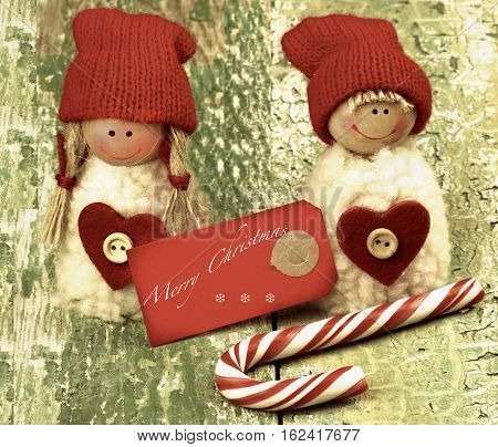 Christmas Decoration Concept with Handmade Dolls in Knit Hats Striped Sweet Cane and Greeting Card with Inscription closeup on Rustic Cracked background. Retro Toned