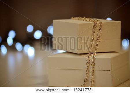 Gift box with a gold chain on a background of lights