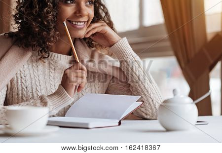Writer creating a novel. Smiling young inspired African American woman sitting in the cafe and being covered with a blanket while making notes in the notebook