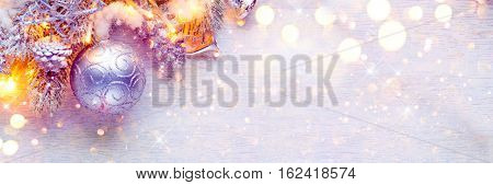 Christmas and New Year Decoration over white wood background. Border art design with holiday baubles. Beautiful Christmas tree closeup decorated with ball, holly berry, tinsel. Pastel colors, vintage.